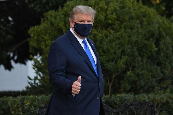 Tổng thống Trump chào phóng viên trước khi bước lên trực thăng đến bệnh viện hôm 2/10. Ảnh: AFP.