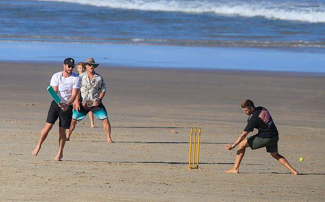 Chris, Liam và anh trai cả Luke Hemsworth (áo hoa) chơi bóng trên bãi biển.