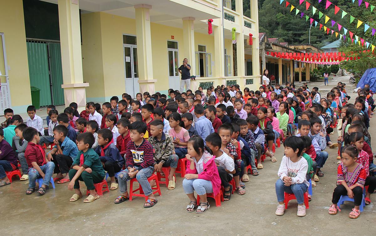 Ngày 30/9, từ sáng sớm, học sinh trường iểu học Chiến Phố, huyện Hoàng Su Phì có mặt tại sân trường. Hơn 100 học sinh hào hứng khi tiết chào cờ thêm chương trình trao tặng sách giáo khoa, bữa ăn xế, xe đạp. Các em mặc đồng phục, lấy ghế nhựa xếp thành hàng ngay ngắn.