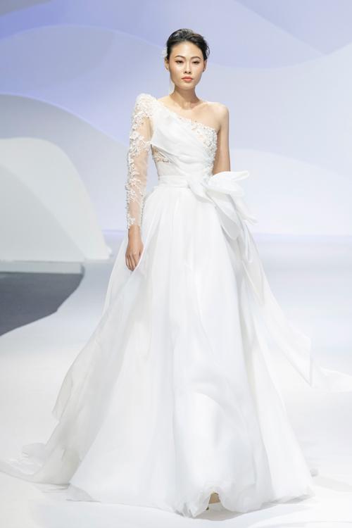 Dáng váy dễ dàng phù hợp với mọi vóc dáng của nàng dâu được điểm xuyết hoa ren dây leo điệu đà nơi ngực và tay áo. Váy thiết kế theo phong cách tối giản nhưng không đơn điệu.