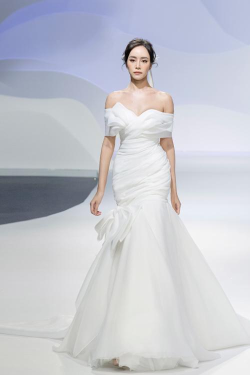 Mẫu váy dáng đuôi cá cách điệu nổi bật với họa tiết 3D nơi ngực áo. Tổng thể thiết kế giống như một bông hoa nở rộ, tượng trưng cho vẻ đẹp căng tràn sức sống của nàng dâu mới.