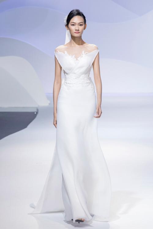 Phần cổ áo cũng là điểm nhấn trong thiết kế này. Váy tạo dáng cúp ngực trái tim nhưng vô cùng kín đáo bởi cách xử lý đan xen chất liệu voan và ren cao cấp.
