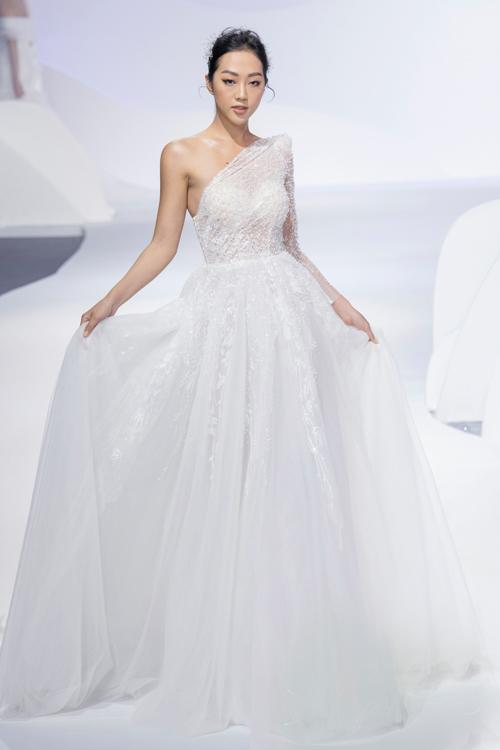 Vẫn với dáng váy lệch vai bất đối xứng nhưng NTK Vĩnh Thụy sử dụng kiểu vai độn nhẹ bắt trend xu hướng thời trang đương đại.