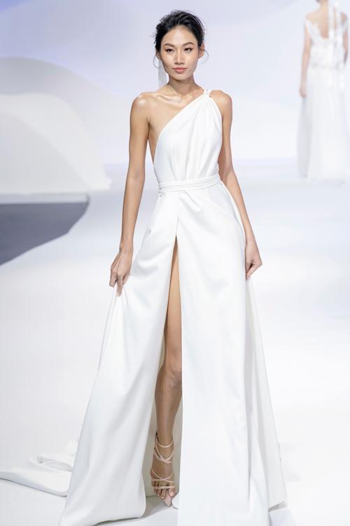 Mẫu váy lệch vai với đường xẻ cao giúp cô dâu khoe khéo đôi chân thon dài.