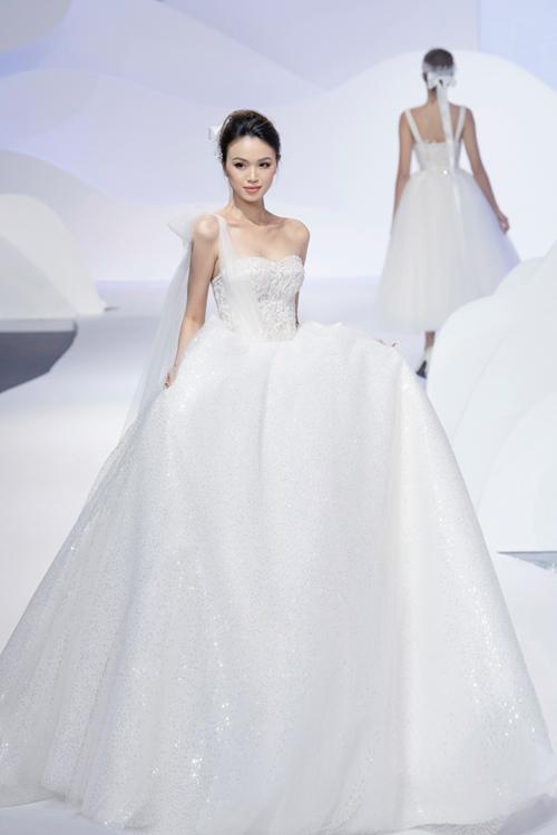 Hiệu ứng bắt sáng tối đa là điều chinh phục các nàng dâu trong thiết kế này, Váy được đính hàng nghìn viên pha lê ở thân trên và tùng váy may bằng vải dệt sequins.