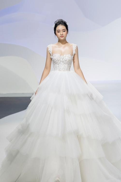 Mẫu váy hai dây có chân xếp tầng bồng bềnh như mây dành cho các nàng dâu muốn hóa thân thành nàng công chúa trong ngày vui của mình. Thân trên của áo được kết từ hàng ngàn bông hoa ren cắt tỉa thủ công tỉ mỉ.