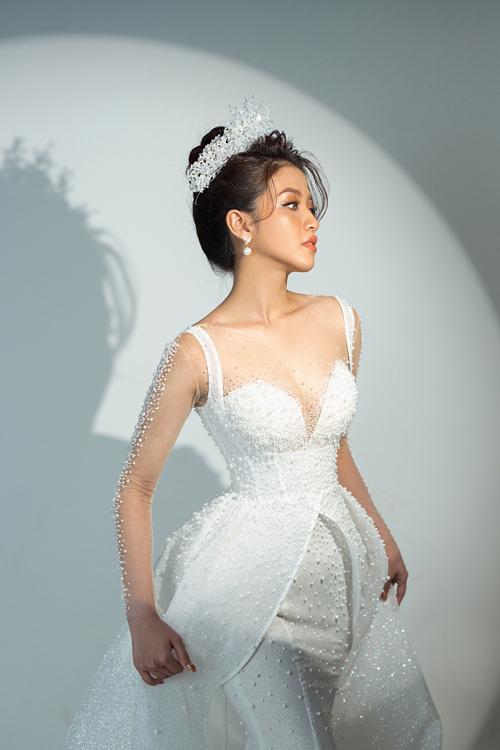 Váy cưới có lớp voan mỏng để NTK và cộng sự đính kết hạt ngọc trên ngực và tay áo. Váy được định hình phom dáng ôm, giúp tôn đường cong cơ thể của nàng dâu. Tóc bới cao giúp nàng khoe khéo đôi vai thon gầy, xương quai xanh mảnh mai.