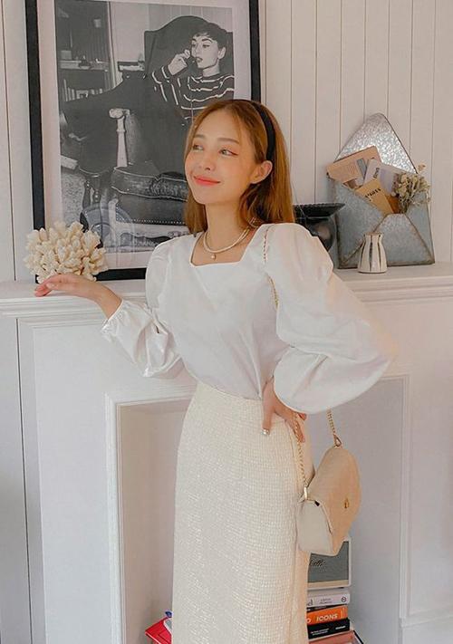 Set đồ trang nhã và dễ giúp các bạn gái có thân hình cò hương trở nên hút mắt với áo tay bồng tông trắng đi kèm chân váy vải tweed.