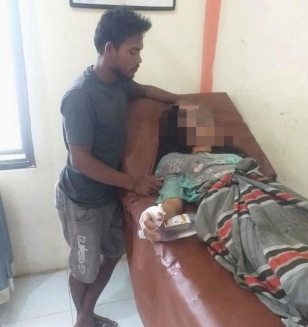Mẹ của cậu bé 9 tuổi nằm điều trị tại bệnh viện sau khi bị hiếp dâm và được chồng chăm sóc. Ảnh: Viral Press.