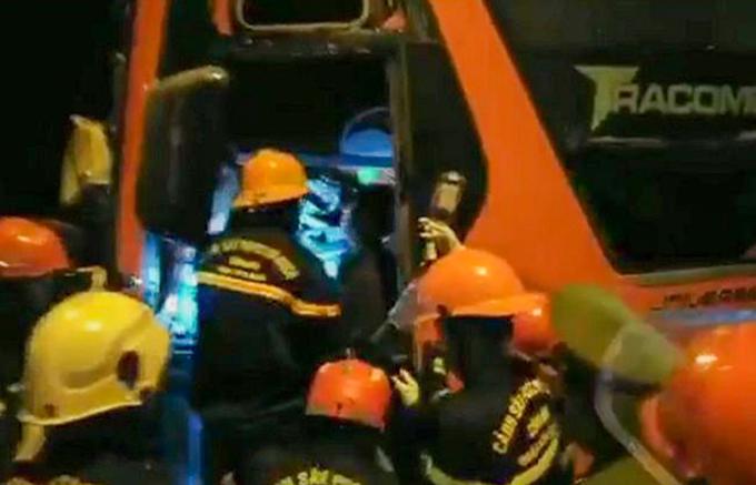 Lính cứu hộ giải cứu tài xế xe khách kẹt trong cabin. Ảnh: Ngọc Hồ.