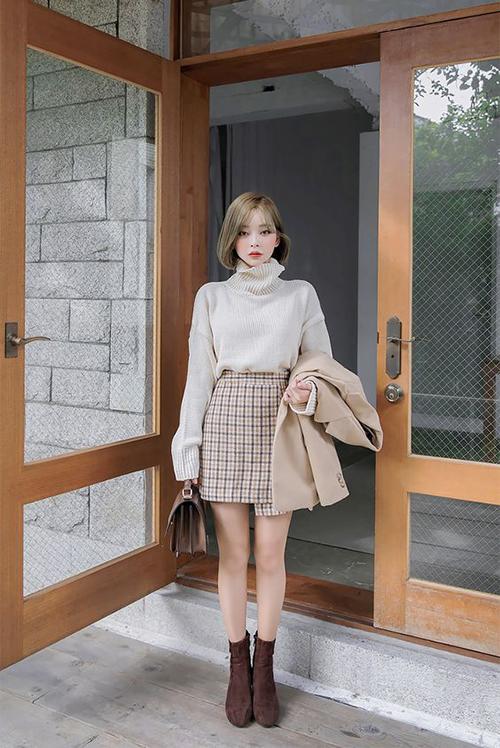 Set đồ đúng chất thu đông cho các nàng văn phòng phía Bắc với áo len cổ lọ, măng tô màu trung tính, chân váy caro và bộ phụ kiện túi xách đồng điệu bốt nâu.
