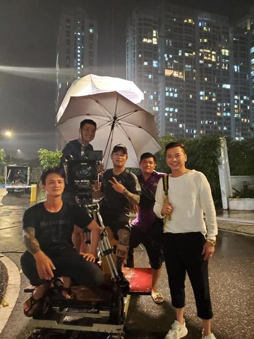 Nghệ sĩ Quang Minh cùng êkíp trong cảnh quay trời mưa. Phim Sugar Daddy và Sugar Baby dài năm tập, dự kiến trình chiếu trong thời gian tới.