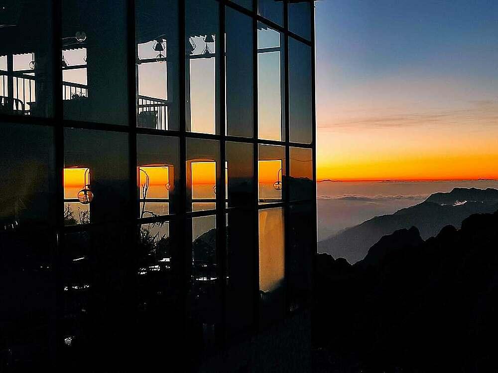 Ngay dưới chân cột cờ trên đỉnh Fansipan có một quán cà phê sân mây nhỏ xinh với khung cửa kính chạm trần chan hòa ánh nắng, ôm trọn cảnh sắc núi non hùng vĩ. Nơi đây thời gian như dừng lại với mùi cà phê thơm nồng và cảm giác an yên, ấm áp khi được tựa vai nhau trò chuyện, ngắm mây dịu dàng trôi bên cửa sổ.