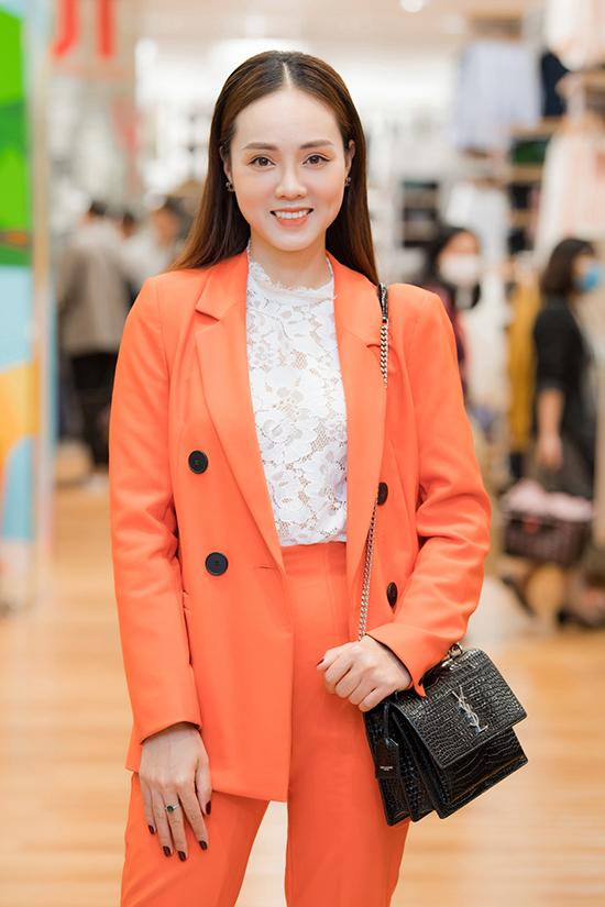 Ngọc Hà - bạn gái của NSND Công Lý - phối túi Saint Laurent cùng bộ suit màu cam bắt mắt.