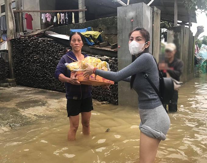 Thủy Tiên lội nước trao vật phẩm cho người dân.
