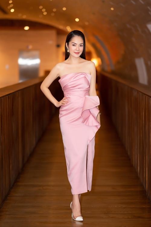 Trước đó, Dương Cẩm Lynh diện đầm hồng cúp ngực trong lúc đón khách.