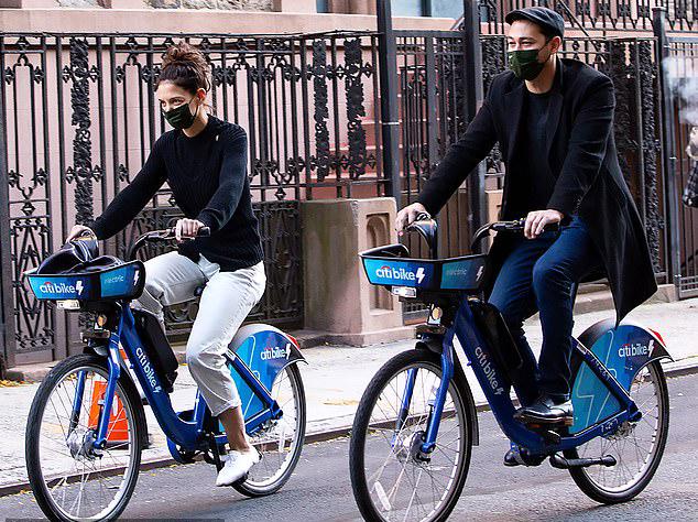 Cặp đôi vui vẻ đạp xe dạo quanh phố phường.