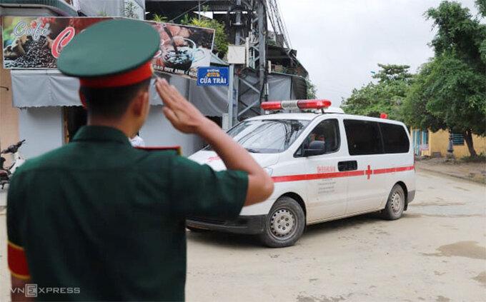 Đồng đội chào điều lệnh khi đoàn xe chở thi thể nạn nhân đi qua, chiều 15/10. Ảnh: Nguyễn Đông.