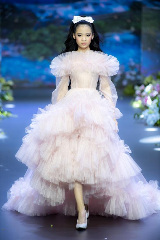 Giữa tiết mục Bảo Hà catwalk với váy voan dài quét đất, gam hồng pastel. Nhóc tỳ cao 1,65 m  nên khi mang giày cao gót, cô bé trông giống một người mẫu trưởng thành.
