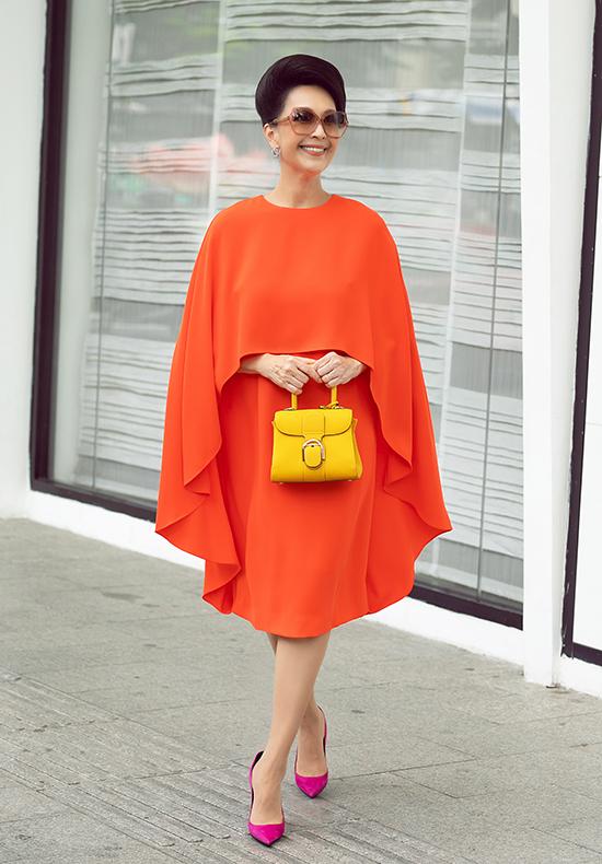 Túi Delvaux xa xỉ màu vàng trở thành nét chấm phá trên nền váy cam. iễm My nổi bật trong thiết kế màu cam, phối phụ kiện theo phong cách color block với t, kính Celine màu nâu khói, giày YSL tông hồng và hoa tai Chanel.