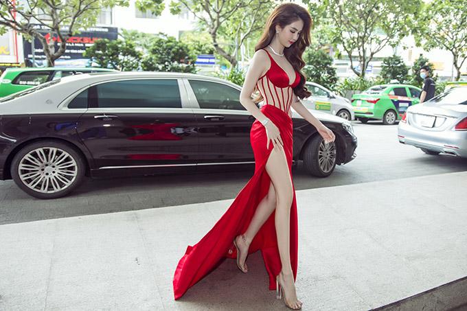 Ngọc Trinh gây chú ý khi xuất hiện ở một trung tâm hội nghị ở quận Tân Bình. Cô mặc bộ cánh đỏ rực, tôn tối đa đường cong cơ thể.