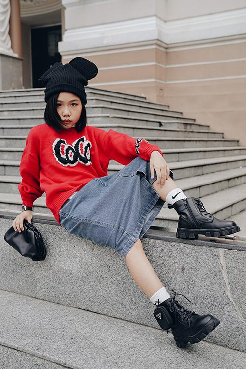 Áo len tông đỏ nổi bật mang lại cảm giác ấm áp được phối cùng chân váy jeans. Phụ kiện đi kèm là clutch, giày và mũ len chuột Mickey đồng điệu sắc màu.