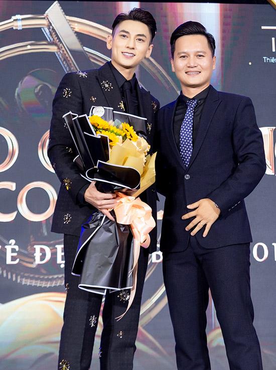 Isaac chụp ảnh cùng đại diện ban tổ chức sự kiện.