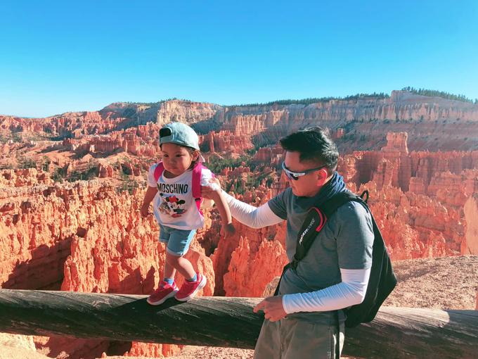 Hành trình lái xe xuyên Mỹ của nhà Thanh Thảo qua nhiều địa danh nổi tiếng như các công viên quốc gia. Một trong số đó là Bryce Canyon National Park, khu bảo tồn rộng lớn ở miền nam bang Utah, được biết đến với những mỏm đá khổng lồ nhọn hình răng cưa màu đỏ cam. Gia đình giọng ca Búp bê biết yêu ghé nơi đây vào thời điểm đẹp nhất trong ngày là lúc hoàng hôn, khi những khối đá chuyển màu cam đỏ rực rỡ. Bé Talia, con gái nữ ca sĩ, bạo dạn đứng trên thành lan can với sự giúp đỡ của bố. Để lên tới địa điểm này, gia đình phải trải qua con đường đi bộ khá dài mang tên Rim Trail nhưng may mắn thời tiết nắng đẹp nên khá thuận lợi.