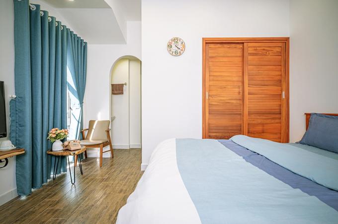 Điểm nhấn nội thất là vật liệu gỗ. Tường được sơn trắng giúp không gian thoáng rộng, sang trọng hơn.