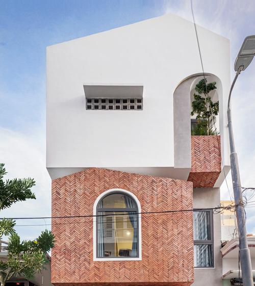 Với những yêu cầu ấy, nhóm KTS đã kết hợp cây xanh trong nhà ở, sử dụng vật liệu thô như khoảng tường màu đỏ gạch, tường xi măng bên ngoài.