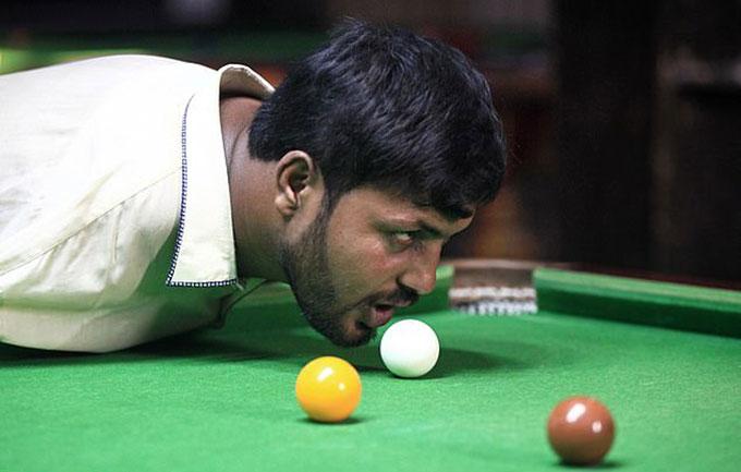 Anh Ikarm chơi bi-a bằng cằm hôm 22/10 ở tỉnh Punjab, Pakistan. Ảnh: Reuters.