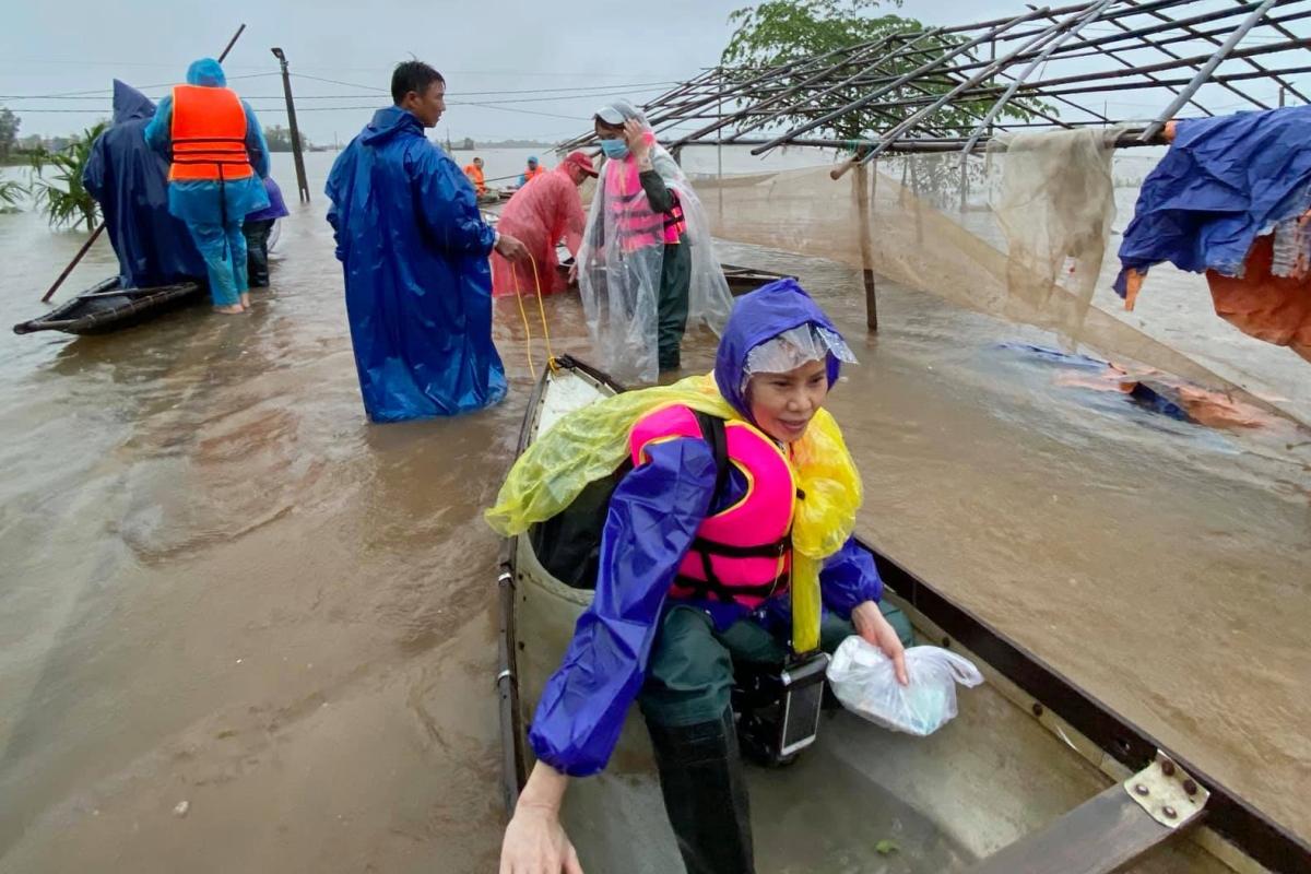 Bà Ngọc Hương, 63 tuổi, không ngại lội nước để trao quà tận tay người dân.