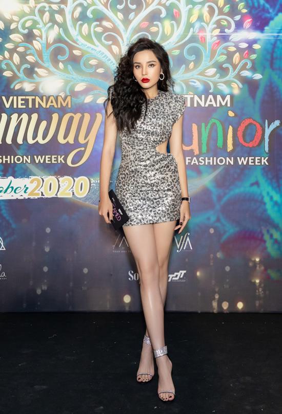 Kỳ Duyên làm tóc xù cá tính và khoe vẻ đẹp gợi cảm trong mẫu váy ánh kim mới nhất của nhà mốt Katy Nguyễn. Hoa hậu có mặt rất sớm tại chương trình để cổ vũ cho siêu mẫu Minh Triệu.