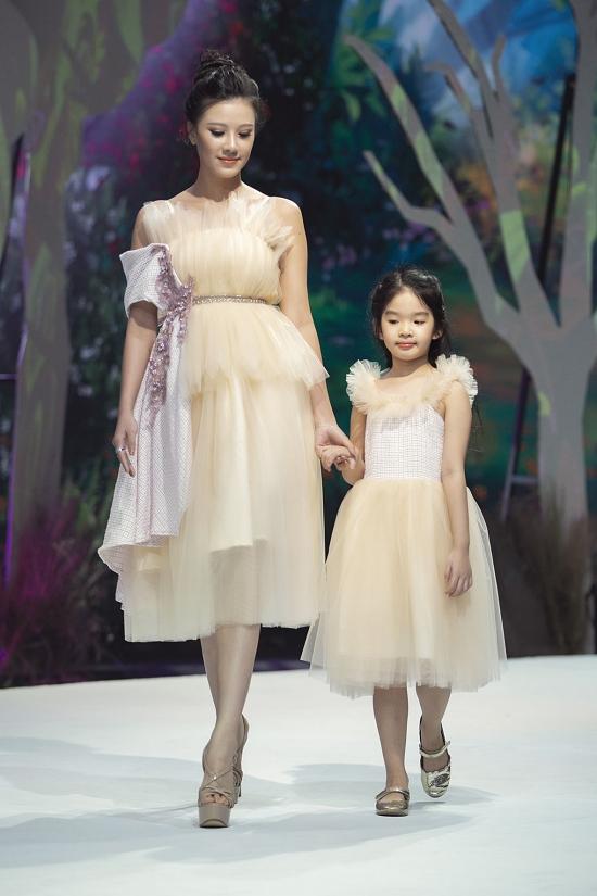 Á hậu Kim Duyên nắm tay bé Thỏ - con gái Xuân Lan - trong một màn trình diễn.