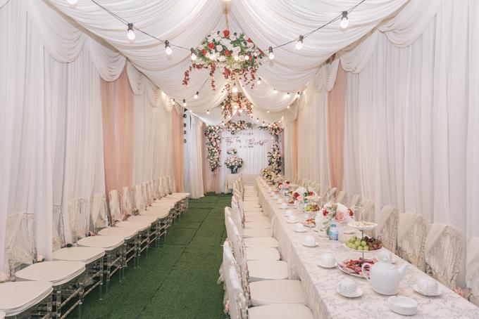 Gia đình cô dâu quyết định chọn lựa trang trí nhà rạp với hoa lụa chủ yếu, có ưu điểm bền, thời gian thi công nhanh, không ảnh hưởng bởi thời tiết. Không gian nhà được sử dụng ghế tàng hình - ghost chair với đệm ngồi, mang đến sự sang trọng.