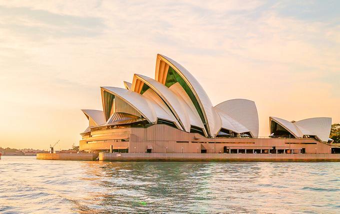 Còn đây là hình ảnh Opera Sydney House thân quen với du khách khắp nơi trên thế giới. Nhìn từ phía trước, nhà hát giống như một con thuyền với cánh buồm trắng xếp so le, khi hoàng hôn buông xuống, ánh nắng chiếu vào như dát vàng lên công trình này. Tòa nhà được xây dựng từ năm 1959 và trở thành một trong những địa điểm được check in nhiều nhất thế giới hàng năm.