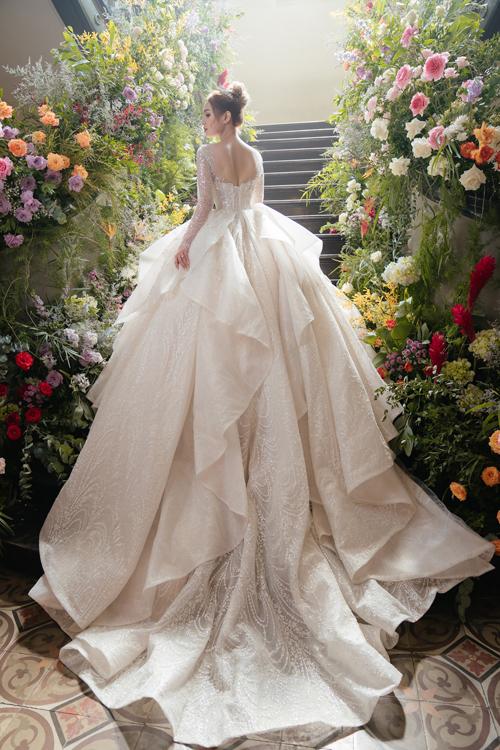 Bộ cánh được ekip sử dụng chất vải sparkle organza nhập từ Italy, mang màu champagne. Váy được đính kết họa tiết lấy cảm hứng hoàng gia, kết hợp 30.000 viên đá Swarovski ánh bạc và pha lê ánh trắng.