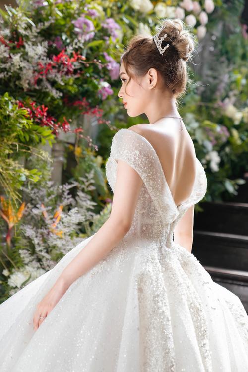 Váy có thiết kế trễ vai tựa đôi cánh mềm mại của thiên nga khi bay lượn trên bầu trời, nhấn nhá bởi 15.000 viên pha lê có độ tán sắc khác nhau, giúp cô dâu có vẻ ngoài sang trọng, quyến rũ.