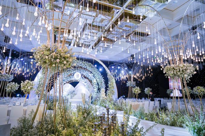 Tiệc cưới khủng của streamer giàu nhất Việt Nam không chỉ được điểm tô bởi hoa lá mà còn có sự xuất hiện của pha lê - hot trend trang trí cưới của năm 2020, tạo nên không gian cổ tích đúng nghĩa cho uyên ương. Hàng trăm ngàn hạt pha lê được đính kết thủ công thành các sợi dây pha lê lung linh. Bối cảnh sân khấu với nhiều vòm tròn lớn được cắt lớp cầu kỳ, xếp lại cùng nhau tượng trưng cho một tình yêu trọn vẹn. Điểm nhấn của không gian chính là 4 cây cổ thụ pha lê được treo tay bởi nhóm 10 người.