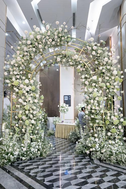 Cổng chào dẫn vào nơi tổ chức tiệc cưới được trang trí toàn bộ bởi hoa tươi. Khung sắt mỹ thuật mạ vàng giúp không gian sang trọng.