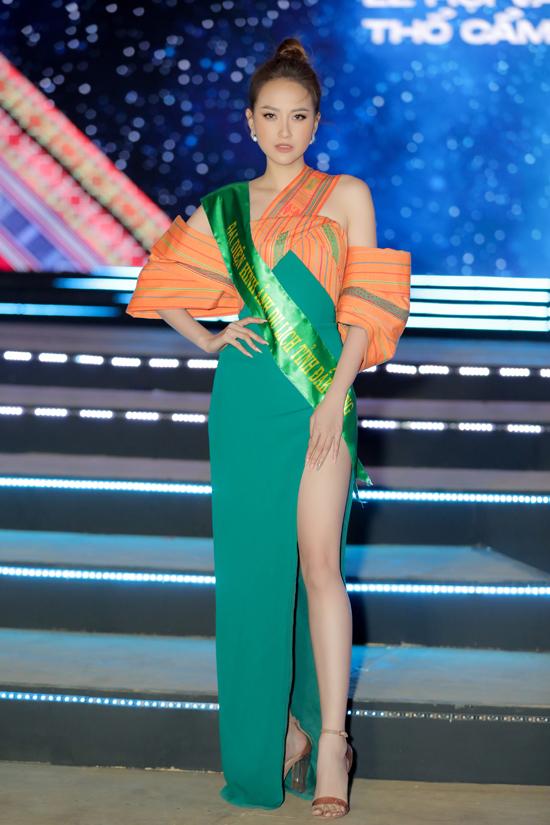 Khánh Ngân diện váy dạ hội kết hợp chất liệu thổ cẩm, khoe chân dài sexy. Trang phục của cô do hai nhà thiết kế Phạm Sỹ Toàn và Huỳnh Bảo Toàn thực hiện.