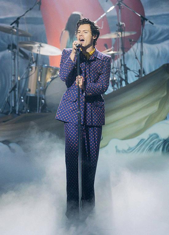 Bộ suit còn được anh thổi làn gió nữ tính bằng họa tiết chấm bi bản nhỏ, không quên tô điểm chiếc khăn nổi bật trên cổ.