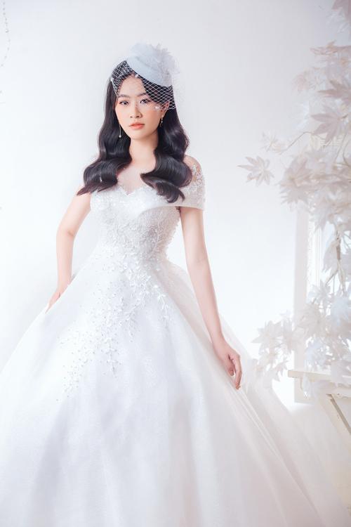 Thạch Thảo thử chinh phục mẫu đầm cưới trễ vai, có chi tiết hoa dây leo dọc thân, đem tới sự nữ tính cho người diện.