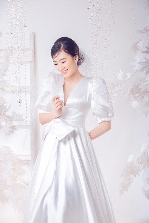 Váy cưới dáng A tay lỡ cổ điển được lấy cảm hứng từ trang phục cưới của các cô dâu hoàng gia. Đây cũng là lựa chọn cho nàng chuộng phong cách tối giản, thanh lịch. Đầm có cổ V, phần eo được nhấn với chi tiết nơ to bản.