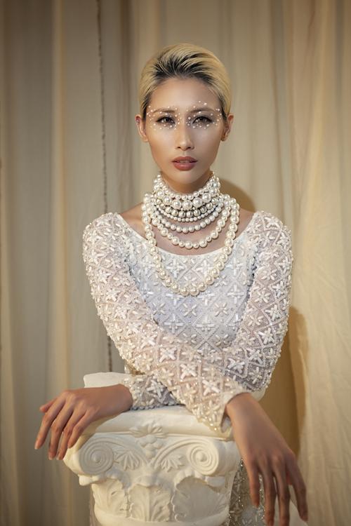 Họa tiết đính kết trên mặt vải giúp tăng hiệu quả bắt sáng khi cô dâu làm lễ. Các trang sức ngọc trai giúp bộ cánh hiện đại mang chút dáng vẻ cổ điển.