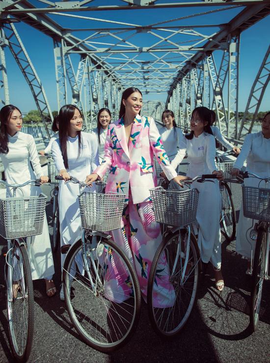 Hoa hậu Tiểu Vy nổi bật bên dàn nữ sinh với thiết kế suit hồng trang trí họa tiết chim én. Vừa kết thúc nhiệm kỳ tại Hoa hậu Việt Nam nhưng Tiểu Vy vẫn là mỹ nhân chiếm trọn tình cảm của khán giả bởi sắc vóc, nét trẻ trung và sự thân thiện, gần gũi.