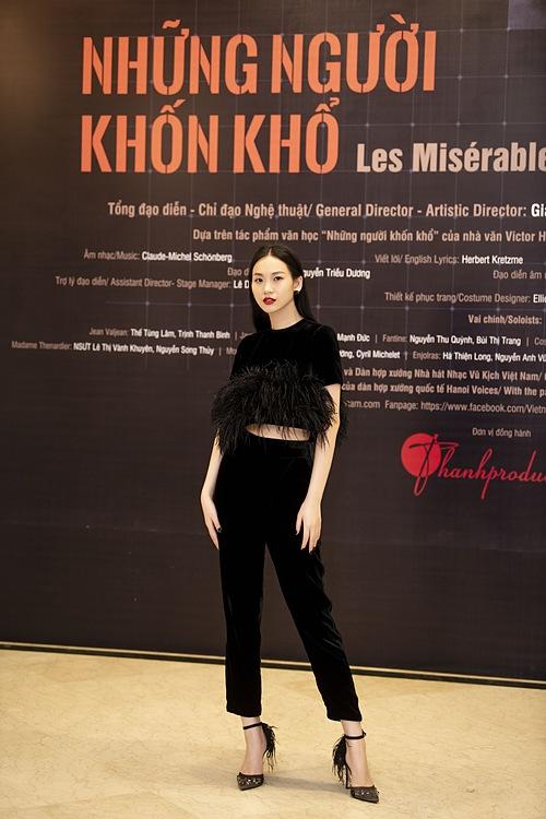 Người đẹp chọn trang phục chất liệu nhung của nhà thiết kế Hà Linh Thư khi đi xem vở nhạc kịch được chuyển thể từ tác phẩm cùng tên của đại văn hào Victor Hugo. Bộ cánh đen đơn sắc, chỉ sử dụng lông vũ cùng tông làm điểm nhấn, giúp tôn lên vóc dáng thanh thoát của fashionista sinh năm 1991.