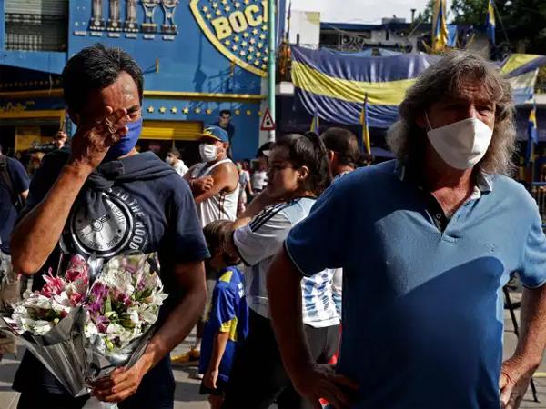Một fan Boca Juniors cầm hoa, gạt nước mắt đứng bên ngoài SVĐ La Bombonera của đội nhà sau khi biết tin huyền thoại Maradona từ giã cõi đời. Cậu bé vàng khoác áo Boca mùa giải 1981-1982, cùng đội bóng vô địch Argentina rồi sang Tây Ban Nha thi đấu cho Barca. 13 năm sau, Maradona trở lại quê nhà và gắn bó hai năm cuối sự nghiệp với Boca Juniors.