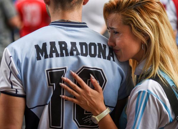 Một phụ nữ nghẹn ngào khóc trên bờ vai người bạn khi cùng những người khác tụ tập bên ngoài SVĐ Diego Armando Maradona ở Buenos Aires.