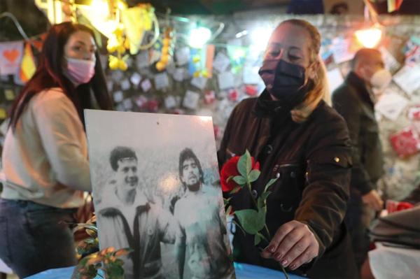 Một người phụ nữ đặt hoa hồng bên cạnh bức ảnh ngày còn thi đấu của huyền thoại Maradona trên chiếc bàn được dùng làm nơi đặt nến, để hoa tưởng niệm Cậu bé vàng.